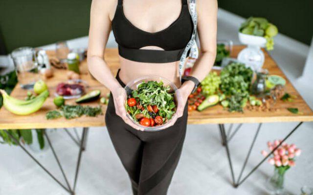 Kobieta ze zdrową żywnością i centymetrem na diecie