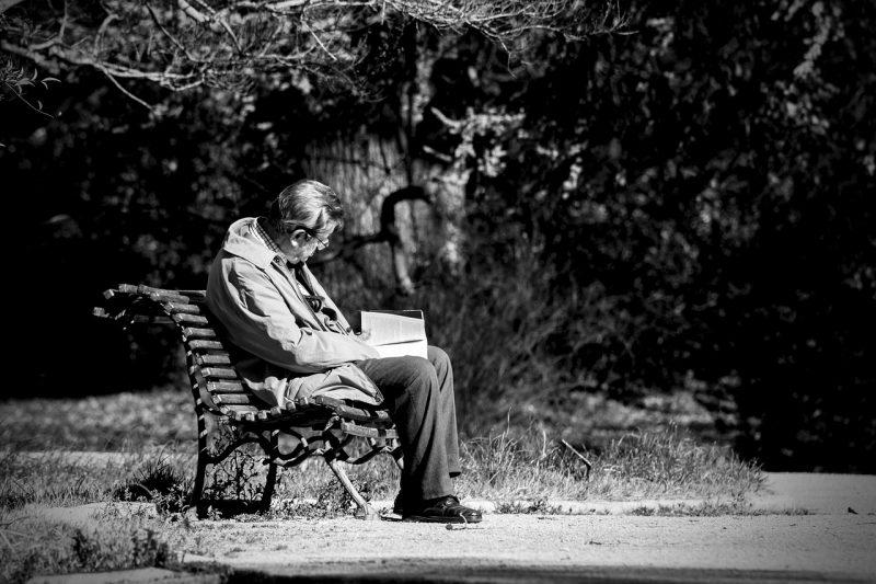 Melancholia. Mężczyzna siedzacy na ławce z książką.