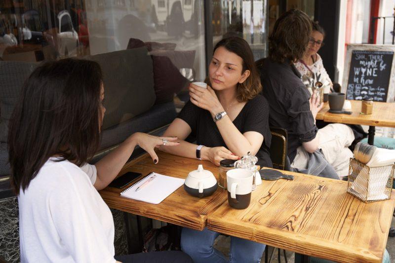Rozmowa. Dwie kobiety przy stole rozmawiające ze sobą.